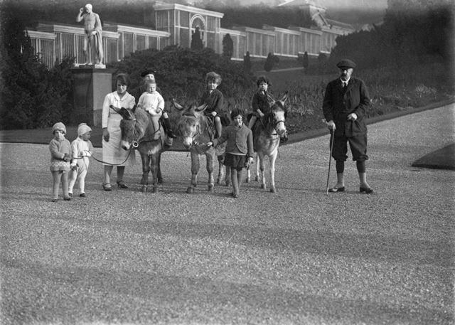 9th Duke of Devonshire with some of his grandchildren riding donkeys in Chatsworth's gardens, 1928