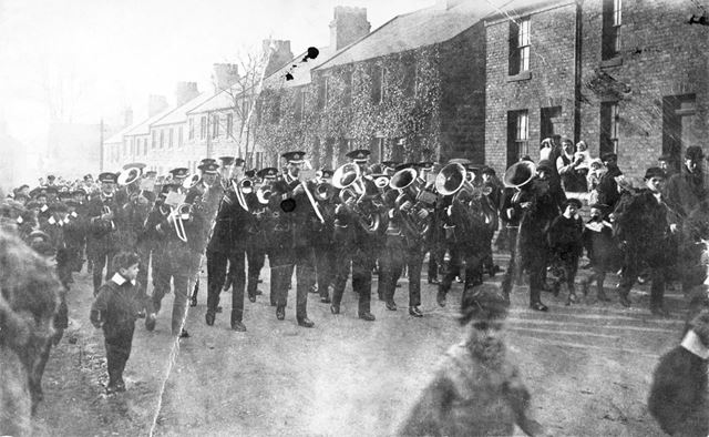 Unidentified event showing a band and men and boys in uniform marching through a Shirebrook Street