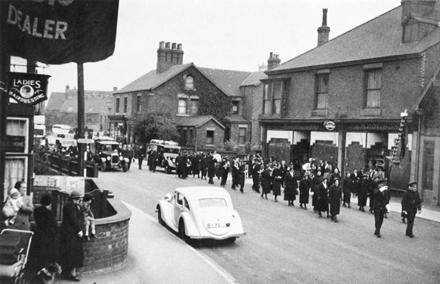 Salvation Army at the head of a Funeral Procession, passing Hodson's Cafe
