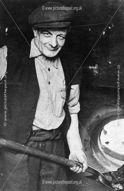 Mr William Bygrave shovelling coal at the Poolsbrook Boiler House