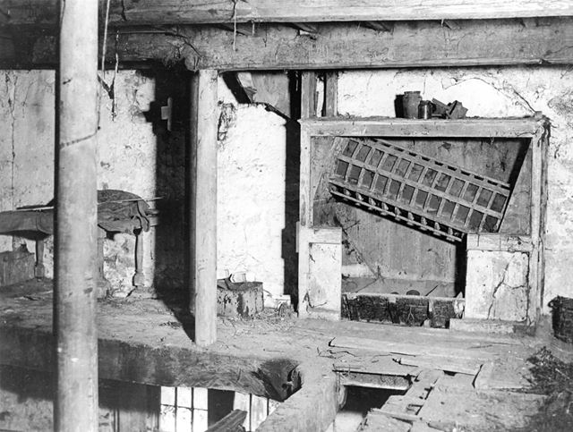 Interior of former mill before restoration, showing old mill machinery.