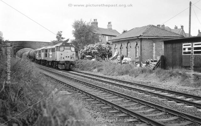 A train passes derelict railway station buildings, Weston on Trent