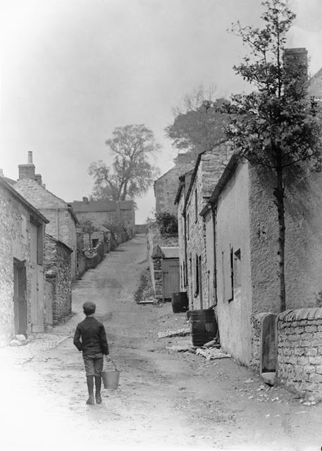 Boy with Pail walking up Village Street, Ashford in the Water, c 1890s