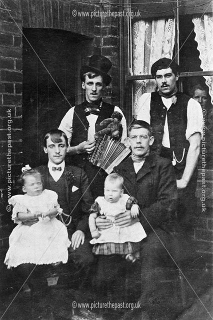 The Grainger Family men and babies sitting outside the back door.