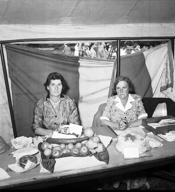 Two ladies with a display of fruit, pork pie and cake at a Stanton Works Annual Flower Show