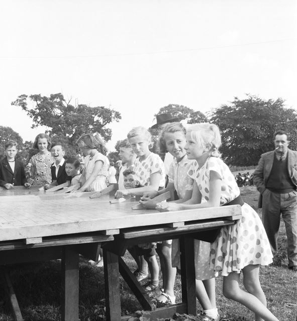 A group of girls playing 'Roller Penny' at a Stanton Works Annual Flower Show