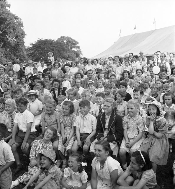 A large group of children (watching the Punch and Judy show ?) at a Stanton Works Annual Flower Show