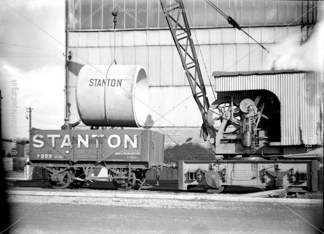 Steam crane loading concrete pipe into a wagon