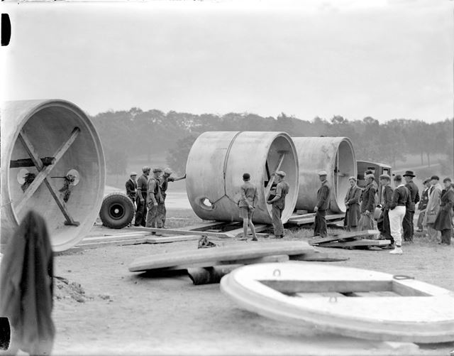 Unloading large diameter concrete pipes for use in air raid shelter construction