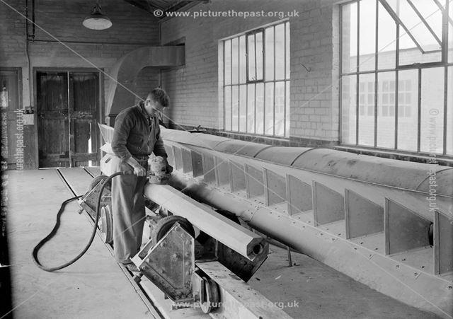 Workman grinding a concrete lamp column, 1939
