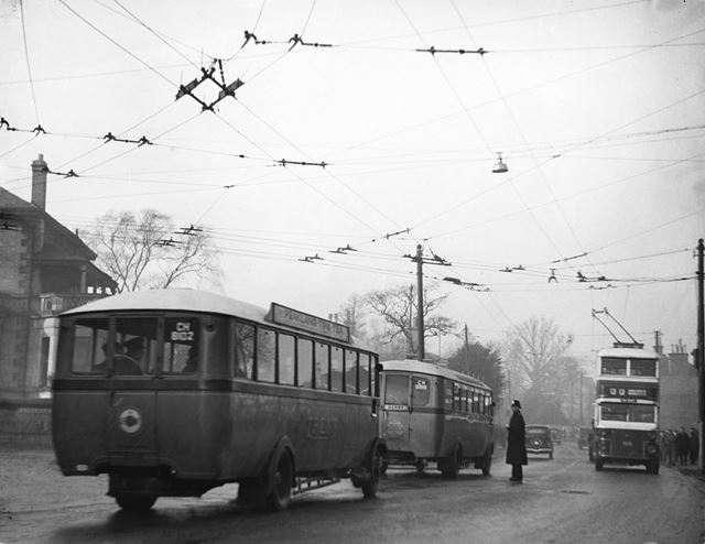 Traffic congestion, trolley bus cables and workers crowd the street on Osmaston Road