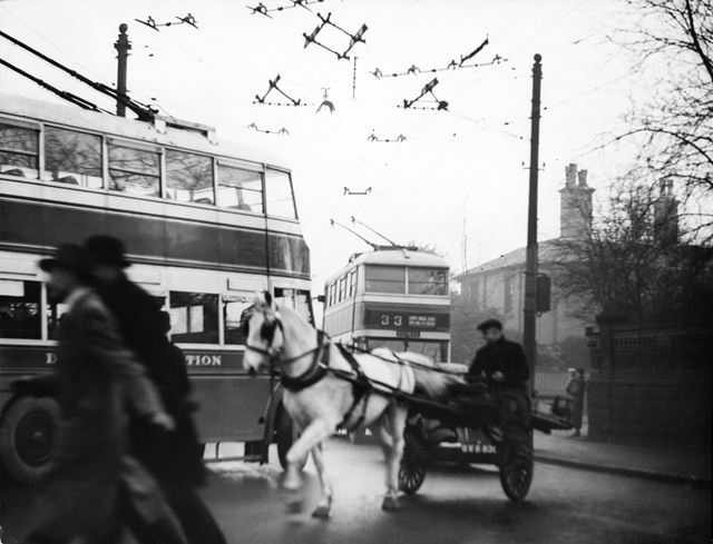 Traffic congestion, horse and cart, trolley buses and workers crowd the street on Osmaston Road