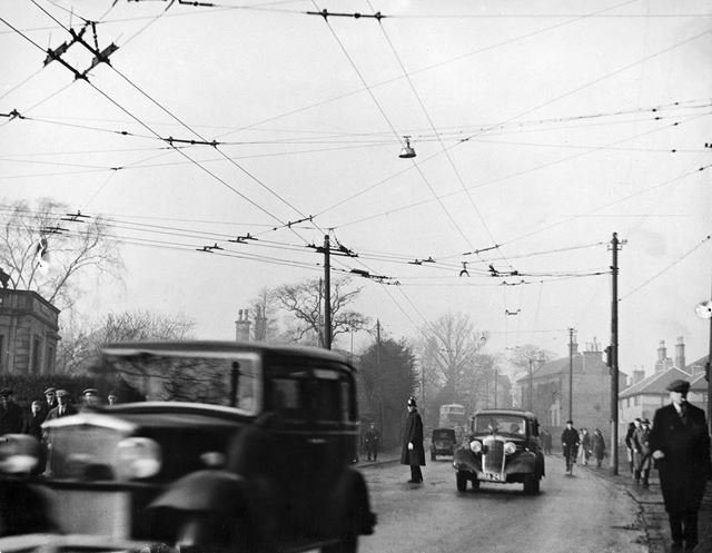 Cars, trolley bus cables and workers crowd the street on Osmaston Road