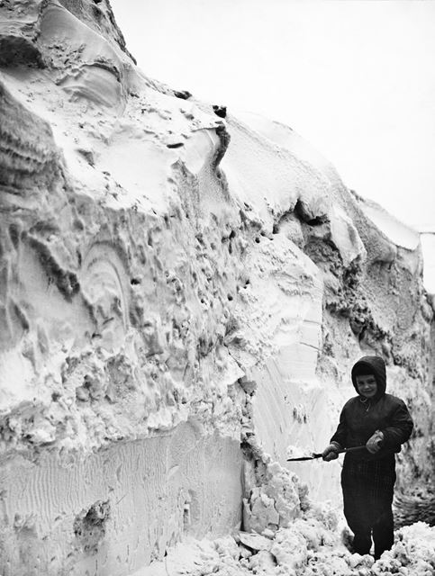 A Young child playing at the side of a huge snow drift, Winter 1963