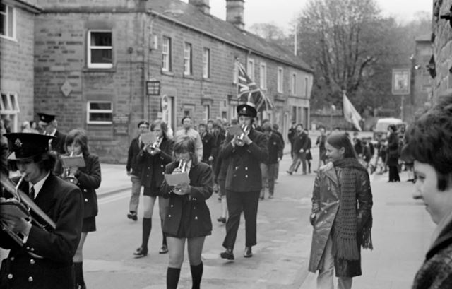 Brownies and Cubs in procession with a band