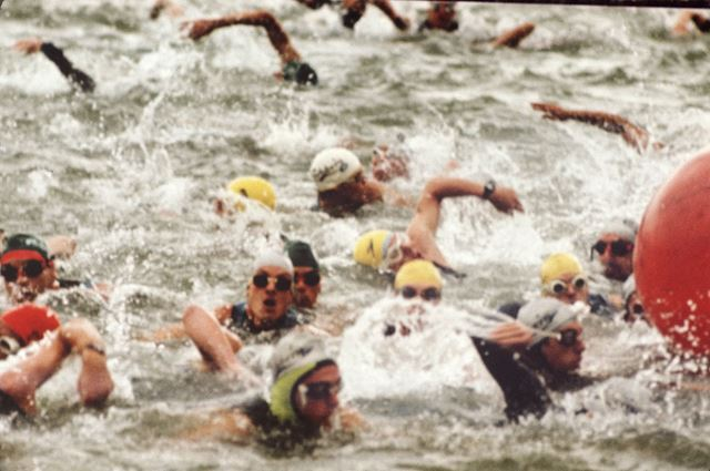 Triathlon event (continuous long-distance swimming, bicycling, and running race) swimmers on the lak